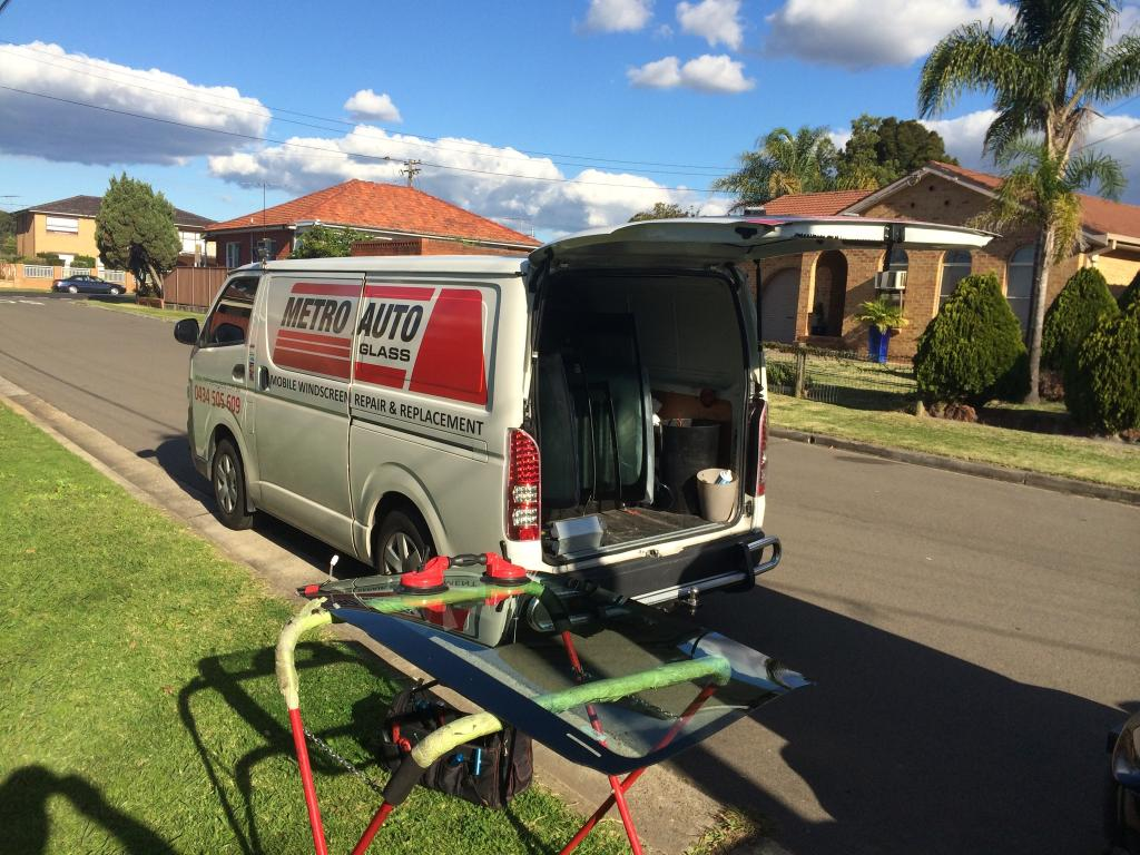 Metro Auto Glass van with back door open and windscreen glass ready to install.