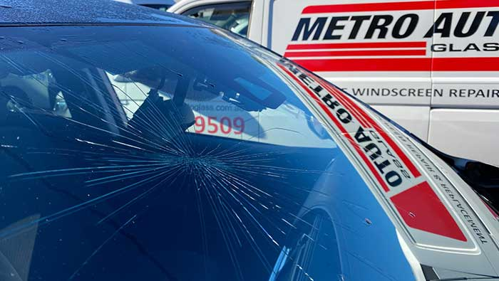 Cracked windscreen glass with Metro Auto Glass van in background
