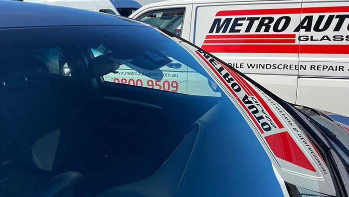 Newly installed windscreen glass with Metro Auto Glass van in background